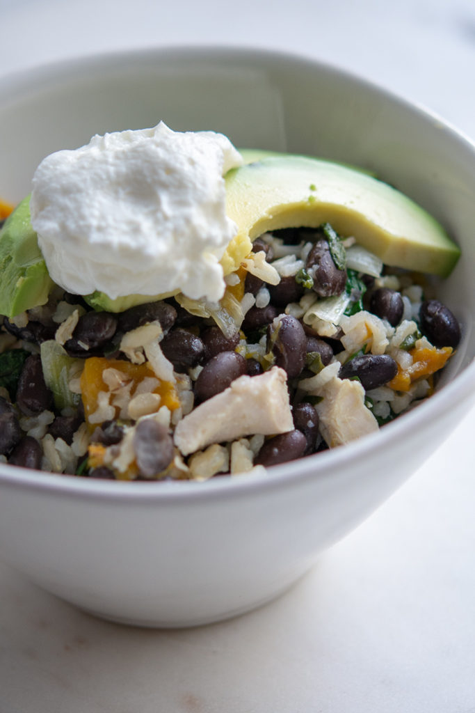 Photo of Chicken and Black Bean Skillet with Brown Rice in a bowl with greek yogurt and avocado