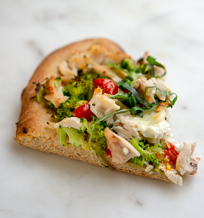 Slice of chicken and broccoli pizza