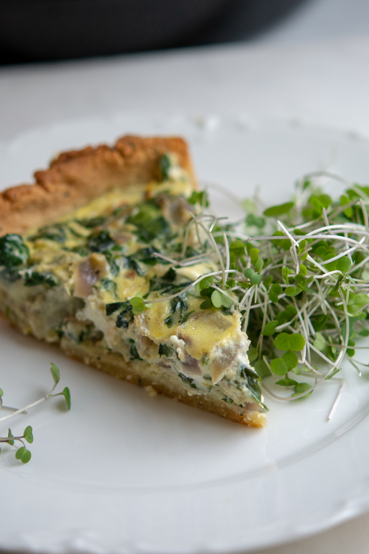 a piece of spinach and artichoke quiche on plate wth microgreens