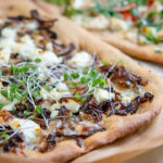 White whole wheat pizza crust with mushrooms, cheese and micro greens