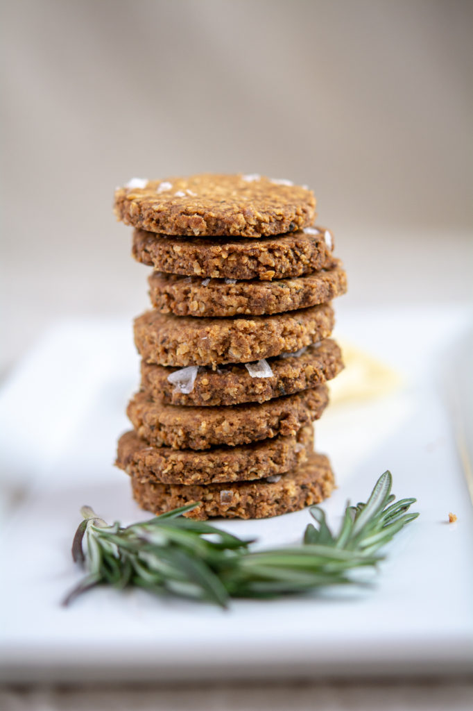 photo of rosemary oat crackers stacked on a white platter with rosemary