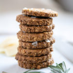 photo of rosemary oat crackers stacked on a white platter