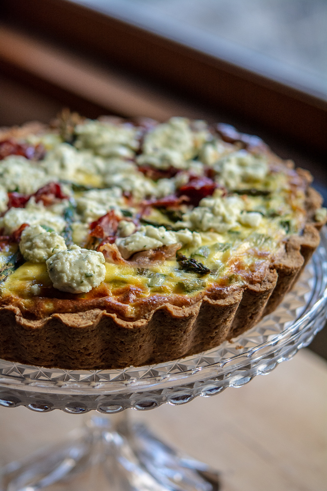Baked asparagus and ricotta quiche on a pretty glass cake stand
