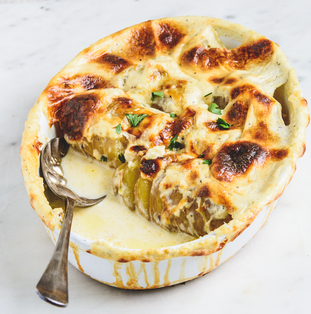 Baked Potatoes Dauphinoise in baking dish with nice spoon