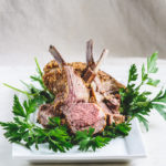 photo of rack of roasted lamb, cut in pieces on a bed of parsley on a white plate