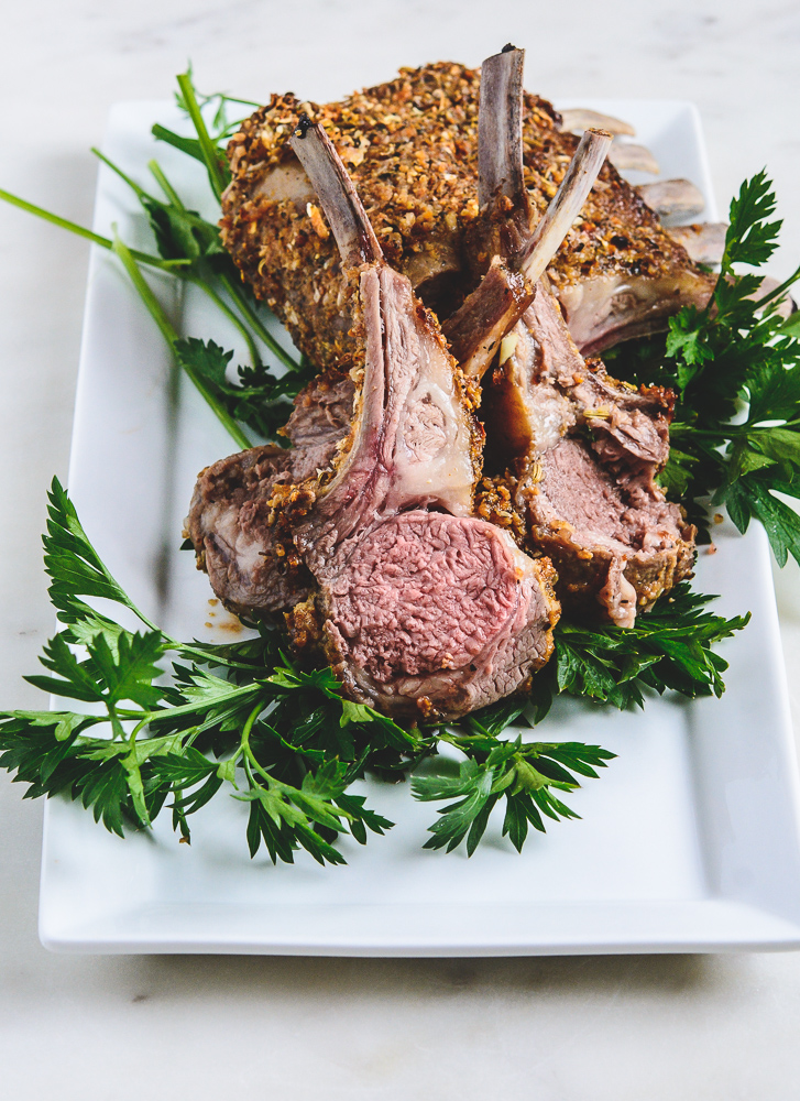 close-up photo of rack of roasted lamb, cut in pieces on a bed of parsley on a white plate