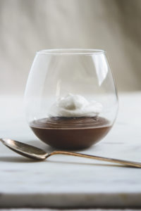 Chocolate Mexican Pots de Creme with whipped cream in a stemless wineglass and a spoon
