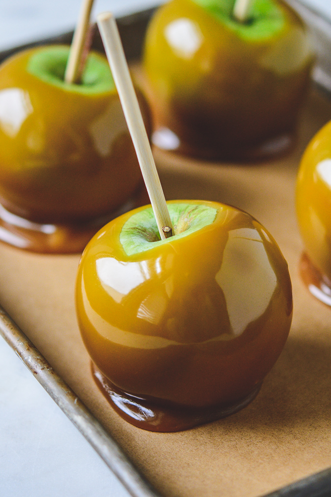 Close up of caramel apple on a rimmed sheet pan
