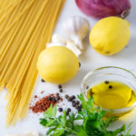 ingredients for pasta al limone: pasta, shallot, lemon, Aleppo pepper, olive oil, garlic, parmesan cheese and parsely