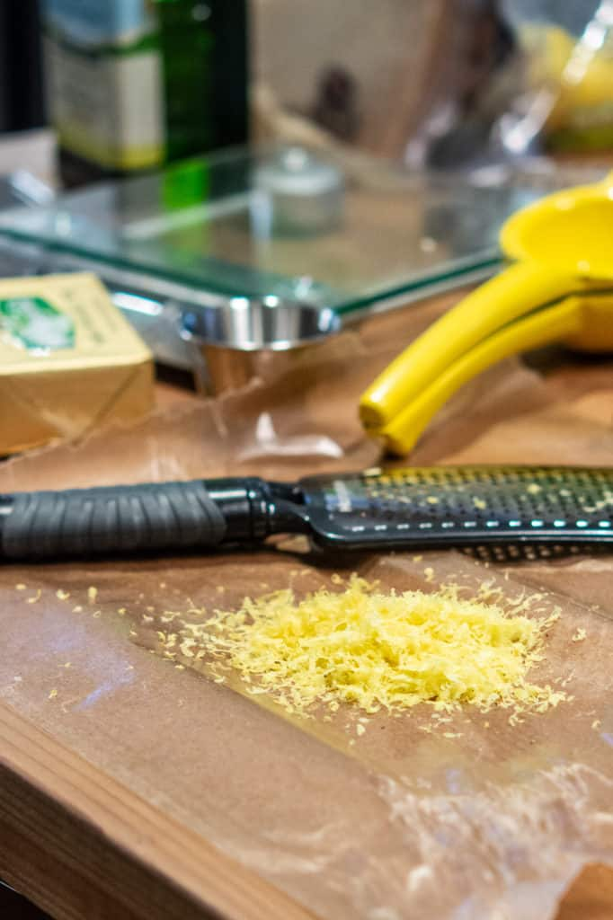 Lemon zest and microplane zester on the countertop.