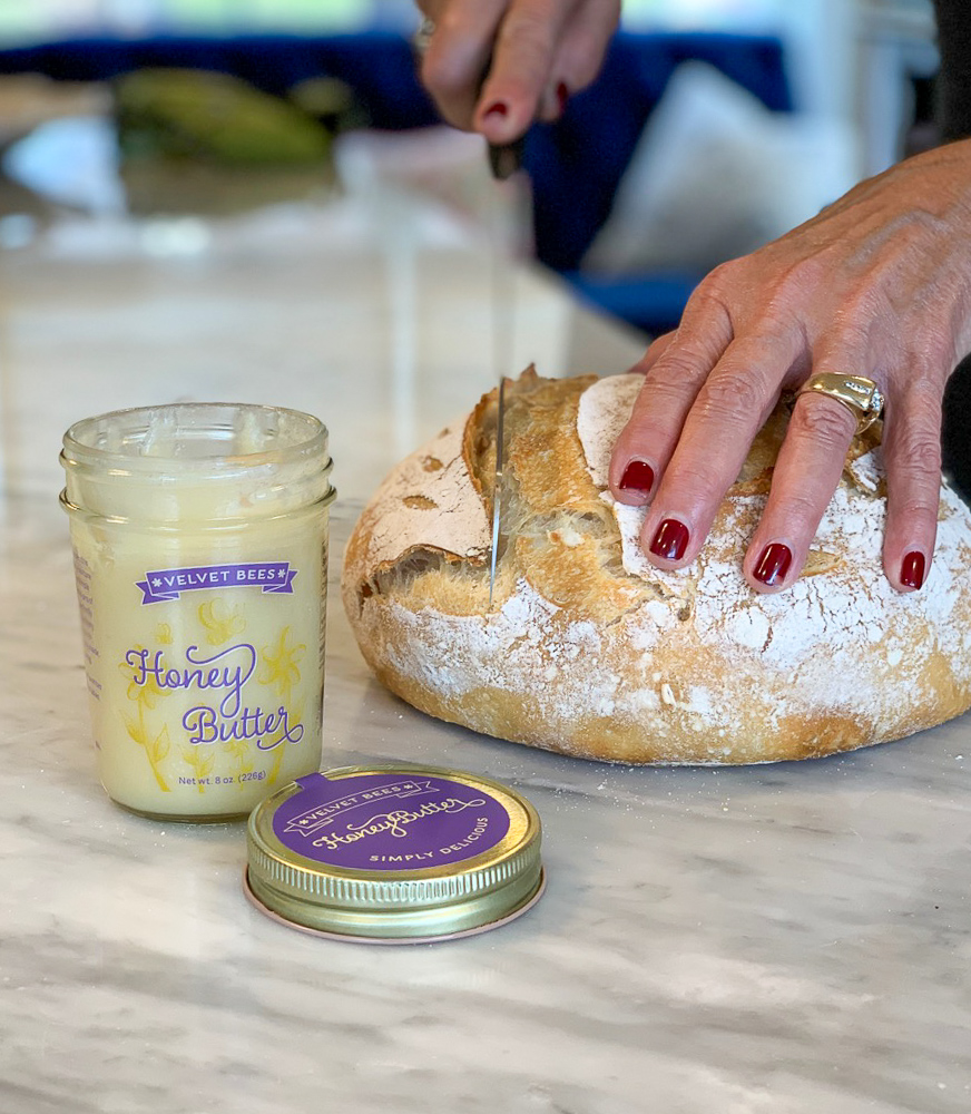 velvet bees honey butter and cutting a piece of fresh baked bread photo