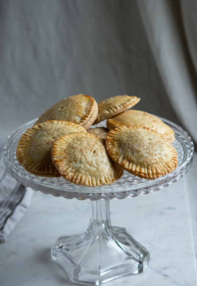 Pumpkin Hand Pies full shot on fancy glass cake plate