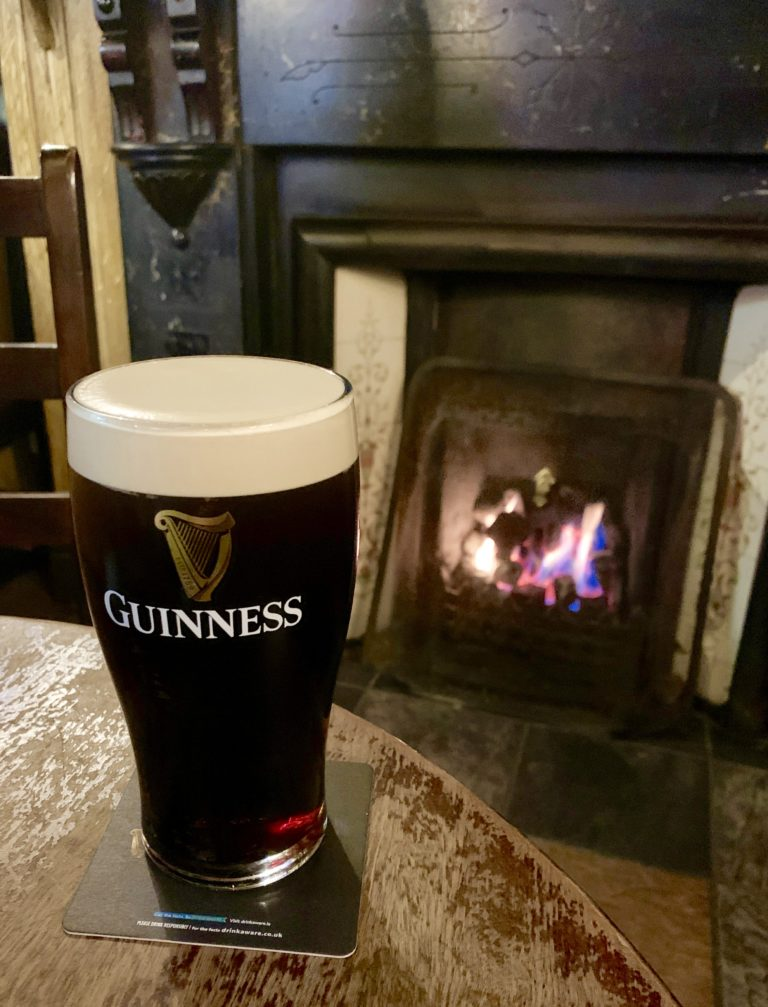 photo of a pint of Guinness in front of the fire