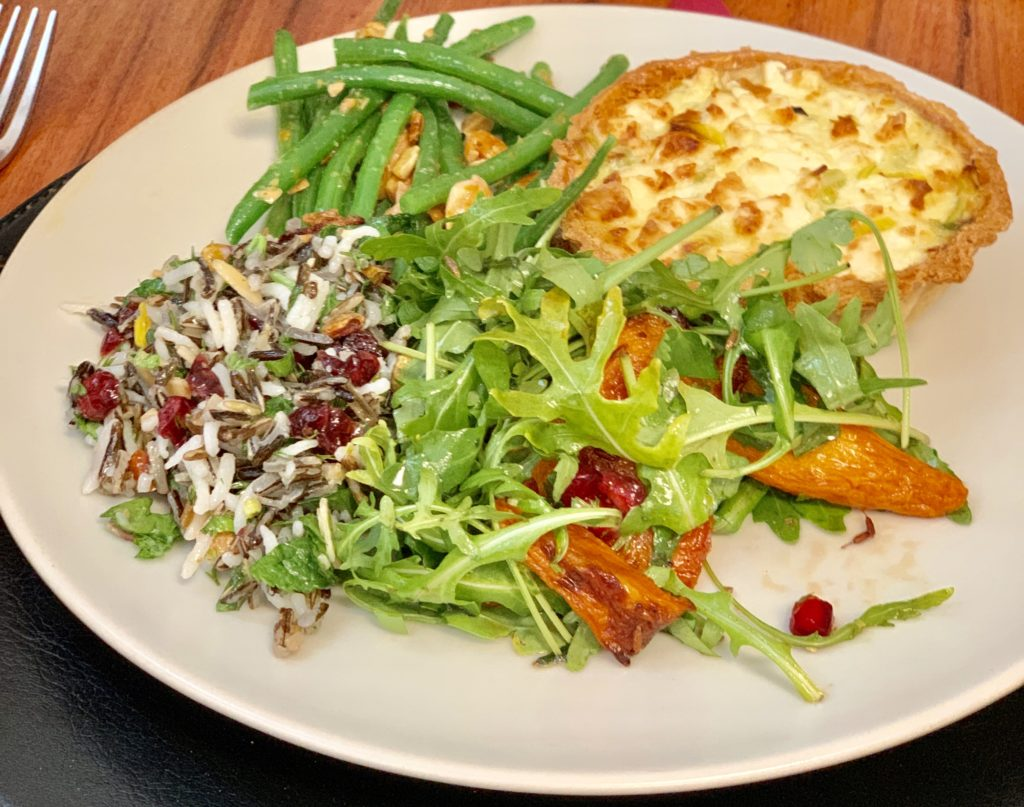 quiche, beans, carrot salad, wild rice and pomegranate salad