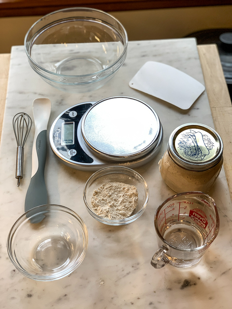 photo of various kitchen utensils for making sourdough bread. bowls, scale, dough scraper, whisk