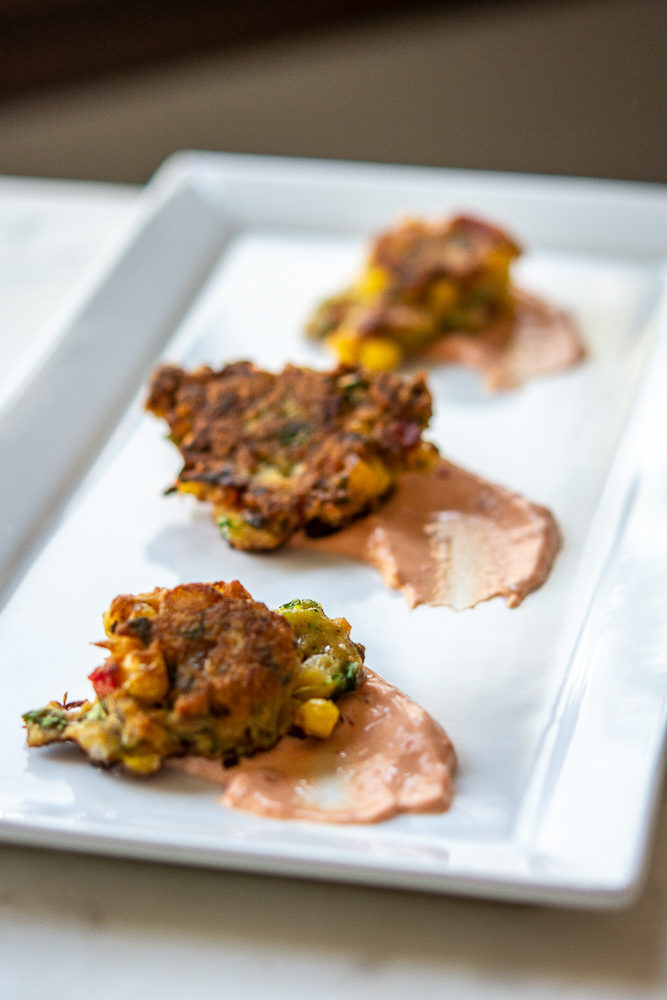 photo of corn zucchini fritters on a white plate