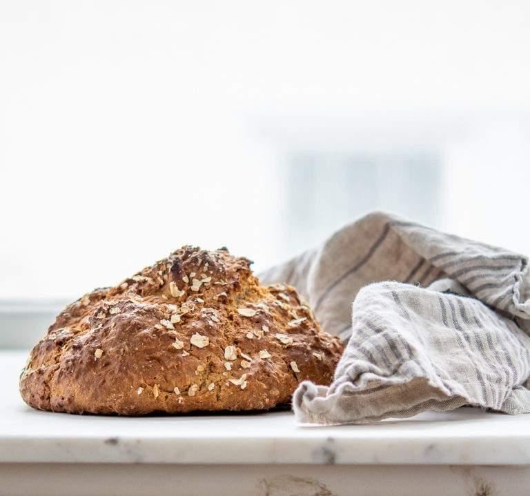 Loaf of irish soda bread next to a kitchen towel