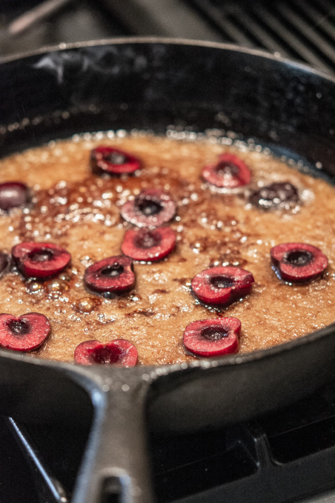 Pineapple Upside-Down Cake cast iron pan with cherries in sugar and butter