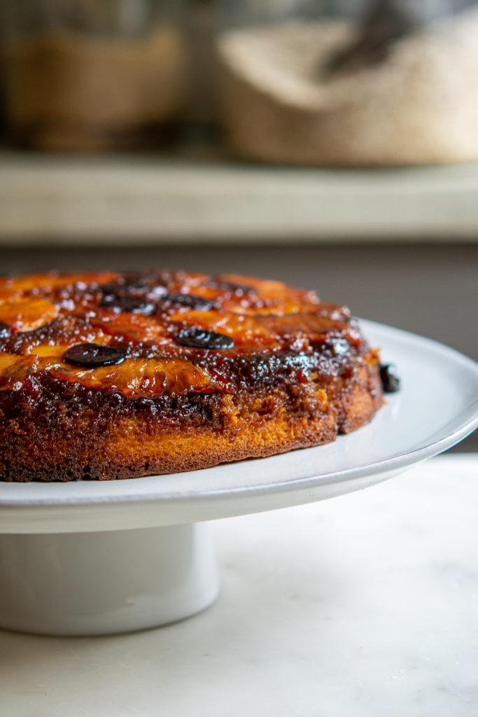 Kitchen shot of Pineapple Upside-Down Cake on cake plate