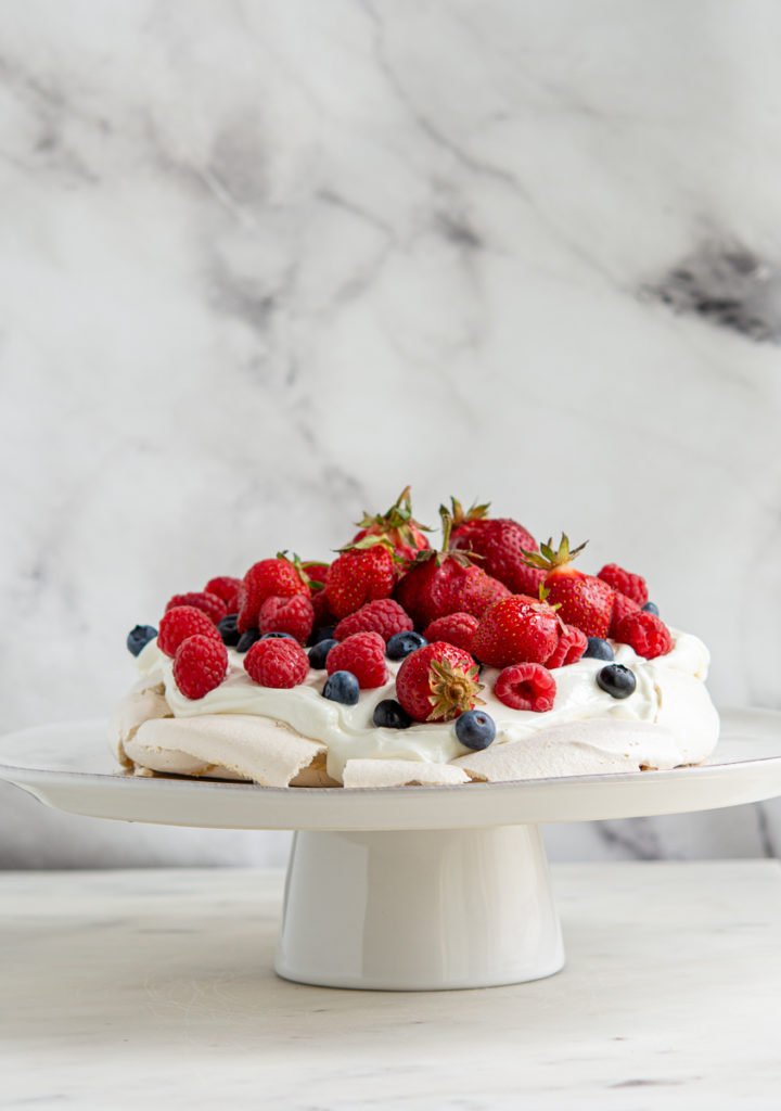 berry pavlova on a cake plate