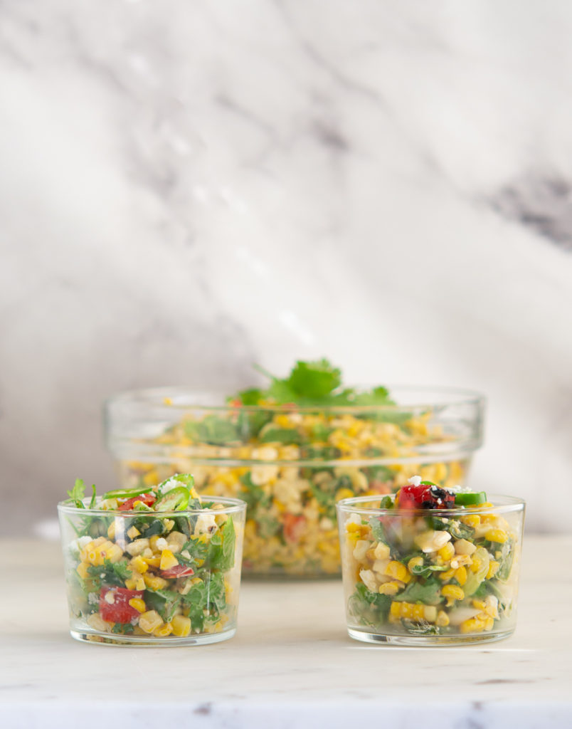 Straight on shot of two Grilled Elote Corn Salad in glass dishes with larger bowl behind