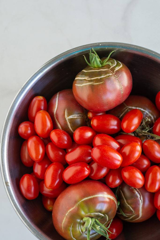 overhead shot of a bowl of garden fresh tomatoes for Grilled Gazpacho