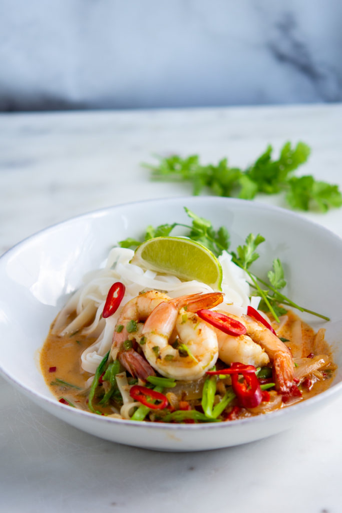 photo of Spicy Shrimp Rice Noodles and Coconut Curry in a bowl with a lime wedge