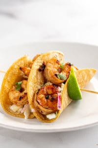 Shrimp tacos on a skewer with lime wedges, side view