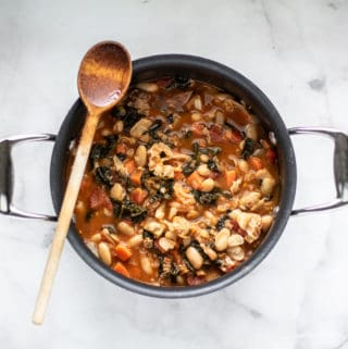 overhead shot of tuscan bean soup in black soup pot with wooden spoon