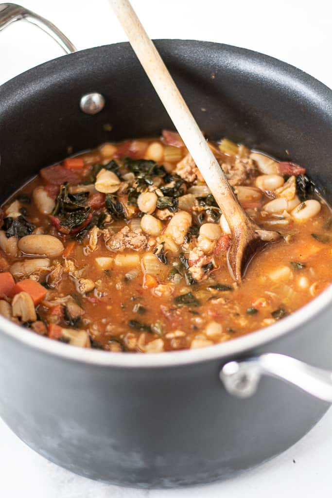 closeup of tuscan bean soup in black pot with wooden spoon