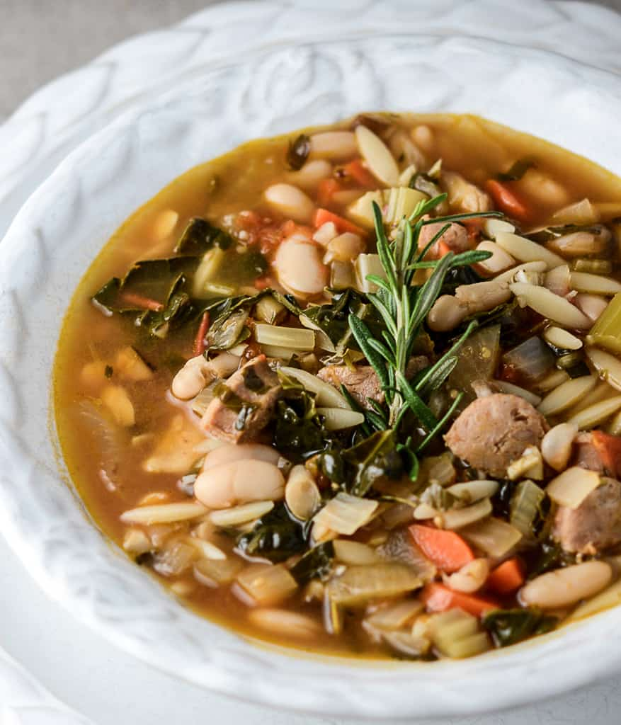 tuscan bean soup in a white bowl with rosemary garnish