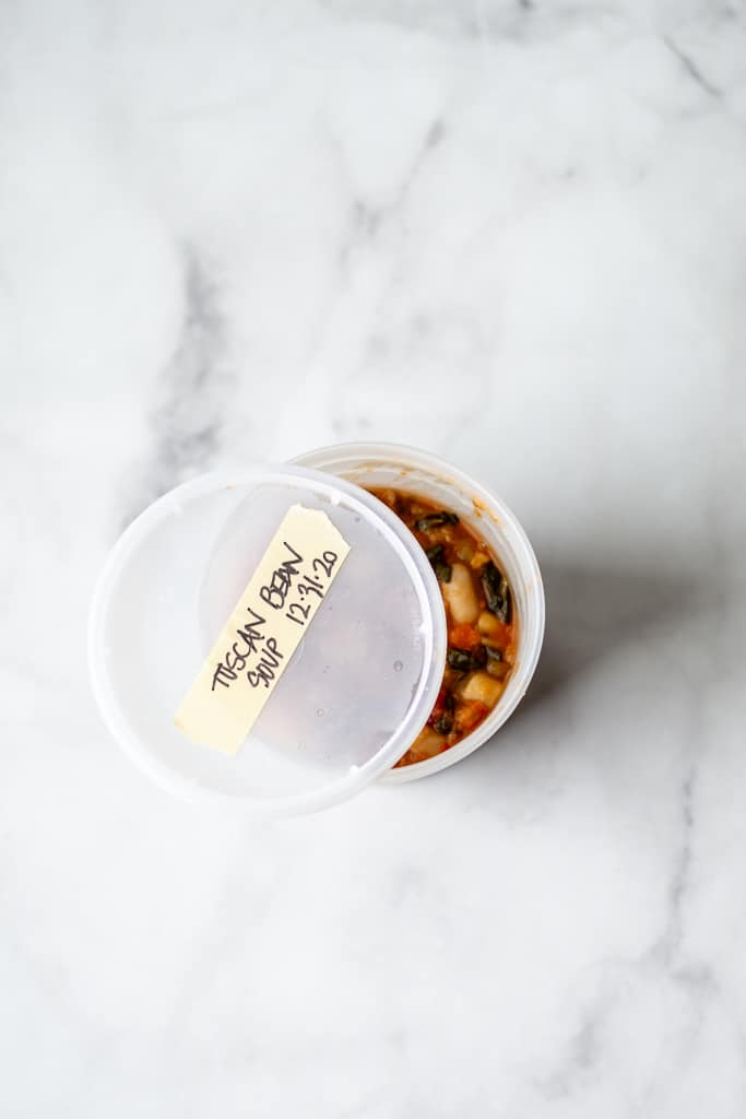 overhead shot of tuscan bean soup in takeaway container, with lid ajar