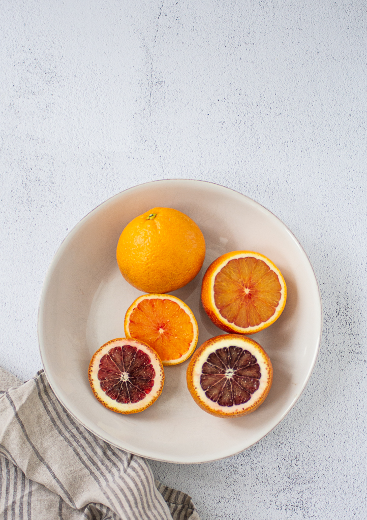blood oranges in a bowl, some sliced, some whole