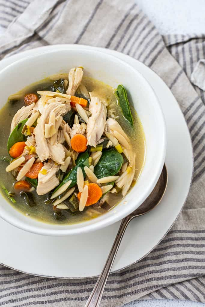 Over head shot of chicken soup with lemon and orzo with spoon and towel