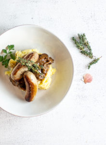 bangers and mash in a shallow bowl with thyme and lucky shell as garnish