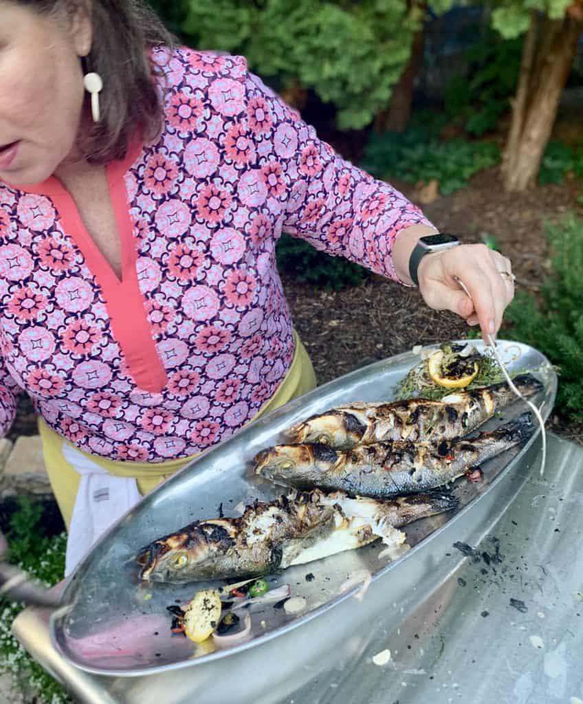 Shelagh holding a tray of whole fish, right out of the pizza oven