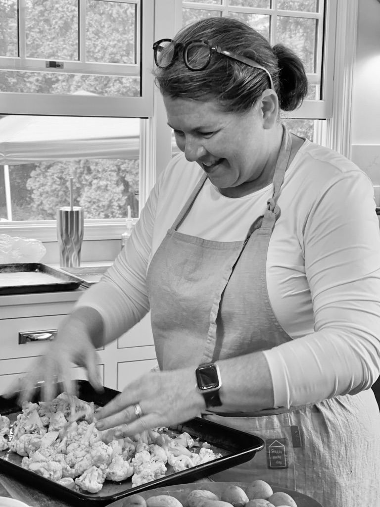 black and white photo of shelagh tossing caulflower in the pan